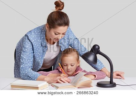 Horizontal Shot Of Experienced Young Mother Leans Near Her Small Child, Helps To Do Home Assignment,