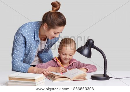 Small Child Rewrites Information In Notebook, Has Pleased Expression, Her Mother Stands Near, Tries