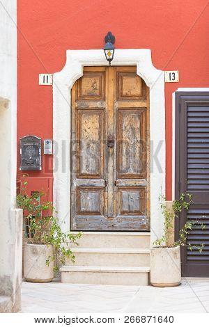 Presicce, Apulia, Italy - An Old Wooden Door And A Bordeaux Facade