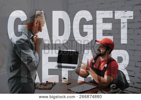 Master And Client Agree About Laptop Repair. Happy Young Computer Repairman Holds Broken Gadget. Old