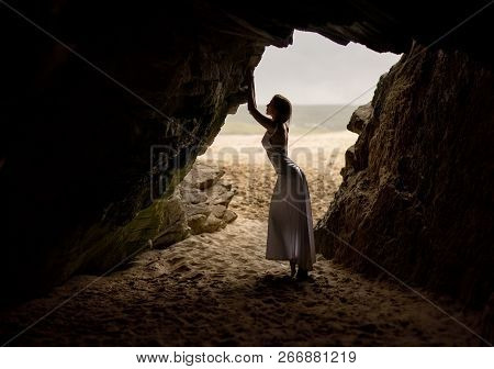 Beautiful And Sexy Woman In Long Dress, Stands And Poses In A Cave Next To A Sandy Beach In Ireland.