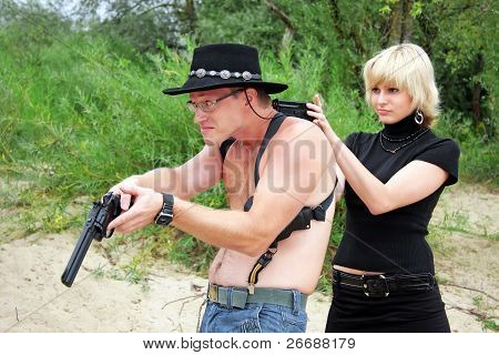 Woman Pointing Gun At Shirtless Man With Revolver