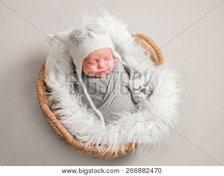 Little cute baby in white knitted beanie covered with gray coverlet sweetly sleeping on white soft  blanket with toy owl in the basket