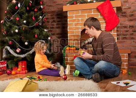 Little girl play with dad  near Christmas tree