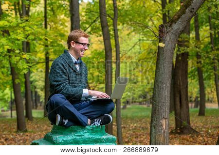 A man with lap top on a pedestal who pretends to be a statue in the the autumn park. Get idea poster