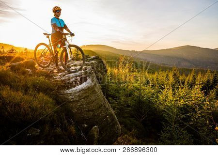 Mountain biking woman riding on bike in autumn mountains forest landscape. Woman cycling MTB flow trail track. Outdoor sport activity. poster