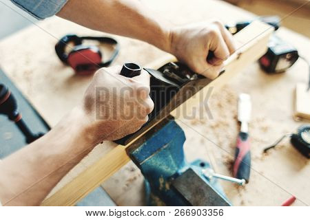 Hands of unrecognizable carpenter measuring wood plank with tape measure and making pencil marks