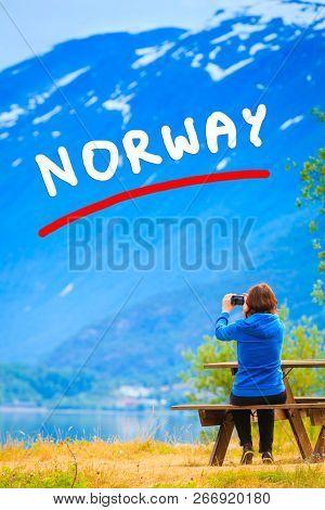 Tourism And Travel. Woman Tourist Taking Photo With Camera, Enjoying Mountains Lake Oppstrynsvatnet