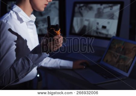 Female Security Guard With Portable Transmitter Monitoring Home Cameras Indoors At Night, Closeup