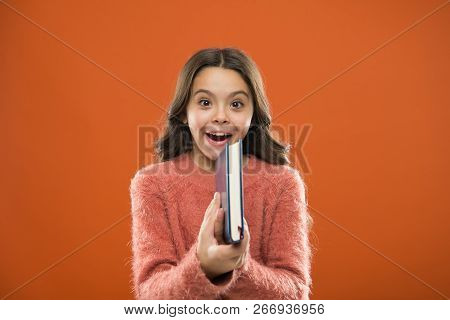 Childrens Literature. Girl Hold Book Read Story Over Orange Background. Child Enjoy Reading Book. Bo