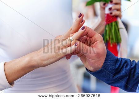 Bride And Groom Marriage Hands With Wedding Rings. Groom Hand Putting Wedding Ring On Bride Finger.