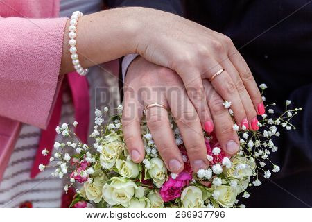 Bride And Groom Hands With Wedding Rings Against Background Of Bridal Bouquet Of Flowers. Declaratio