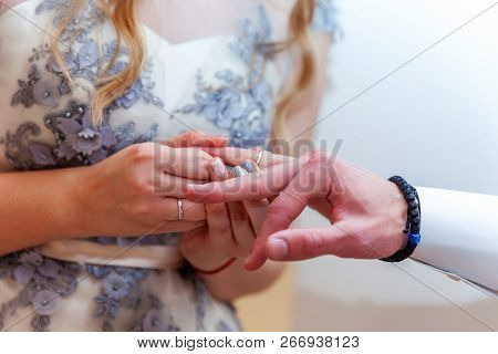 Bride And Groom Marriage Hands With Wedding Rings. Bride Hand Putting Wedding Ring On Groom Finger.