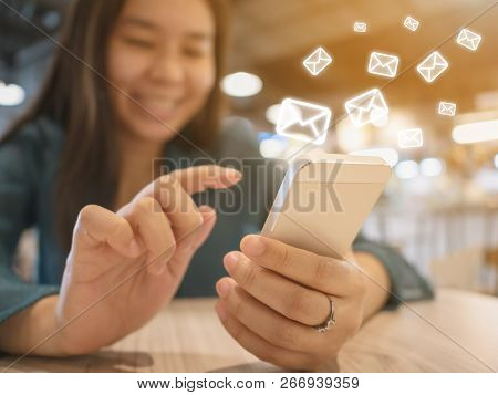 E-mail Marketing And Newsletter Concept. Woman Hand Sending Message And Mobile Phone With Email Icon