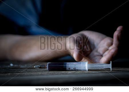 Drug abuse concept, overdose male drug addict hand, drugs narcotic syringe in hand on the floor poster