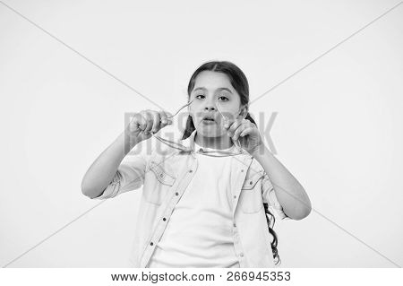 Let Me See. Kid Girl Puts Heart Shaped Eyeglasses. Girl Serious Face Putting Glasses On. Child Serio