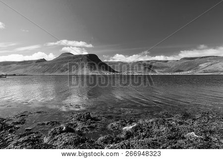 Mountain Landscape Seen From Sea In Isafjordur, Iceland. Hilly Coastline On Sunny Blue Sky. Summer V