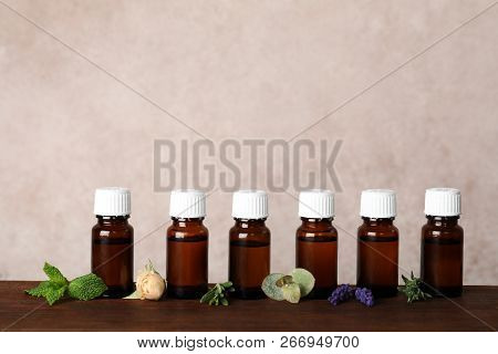 Glass Bottles With Different Essential Oils And Ingredients On Wooden Table. Space For Text