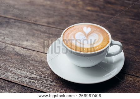 Close Up White Coffee Cup With Heart Shape Latte Art On Grunge Wood Table At Cafe