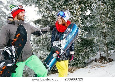 Snowboarders couple in mountain on skiing going to ski terrain