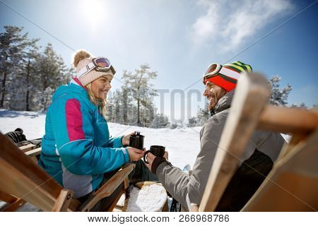 Woman and man on skiing in sunbed in mountain enjoy with drink