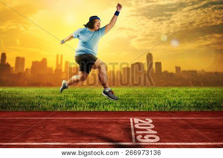 Attractive Asian Fat Man Running On Running Track With 2019 Number On The Start Line. New Year Resol