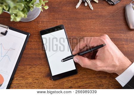 Business Desk With Hand Interacting On A Mobile Phone With Active Capacitive Stylus. Horizontal Comp