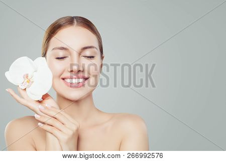 Beautiful Smiling Woman With Healthy Skin, Cute Smile And Orchid Flower On White Background. Spa, Sk
