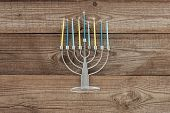 top view of traditional jewish menorah with blue and yellow candles on wooden tabletop, hannukah holiday concept poster