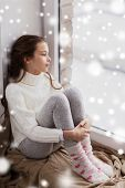 childhood, sadness and people concept - sad beautiful girl in sweater sitting on sill at home window in winter poster