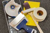 Close up view of painter accessories. Putty knife, masking tape, paint brush, sandpaper. poster