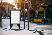 Outdoor empty informational board placeholder with a road and taxi car behind; white blank city billboard mockup; vertical blank advertising banner template on the sidewalk with the crossroad behind poster