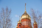 Old red brick Christian church in Kemerovo with golden and gilded domes against a blue sky and tree branches. Concept of faith in god, orthodoxy, prayer poster