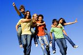Group of happy youth having fun piggyback race outdoors poster