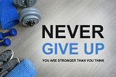 Never Give Up. You Are Stronger Than You Think. Fitness motivational quotes.Sport theme. Healthy and active lifestyle concept. Sneakers, blue dumbbells and a workout mat on grey wooden background. poster