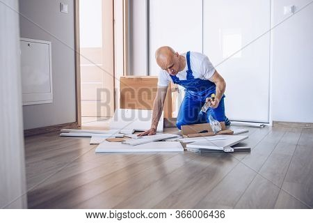 Nervous Man Assembling Cabinet And Reading Manual