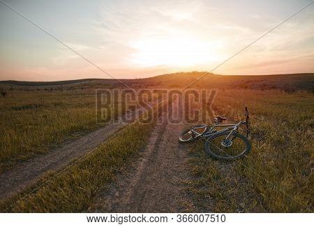 Mountain Bike Lies On The Ground During Beautiful Sunset On The Horizon. Mountain Bicycle