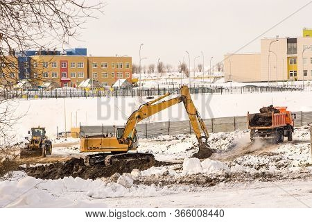 In Winter, Earthwork Is Carried Out At The Construction Site, Frozen Soil Is Removed When Digging A