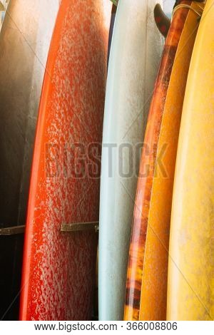 Set Of Multicolored Surf Boards In A Stack By Ocean.bali.indonesia. Red, Orange, White Surf Boards O