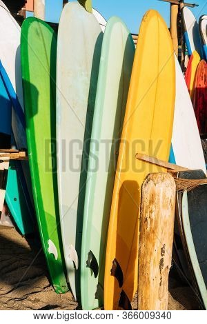 Set Of Different Color Surf Boards In A Stack By Ocean.bali.indonesia. Surf Boards On Sandy Beach Fo
