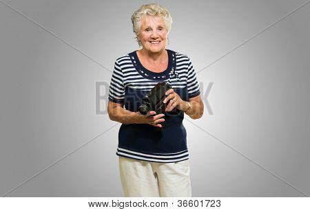 Happy Senior Woman Standing With Video Camera Isolated Over Gray Background