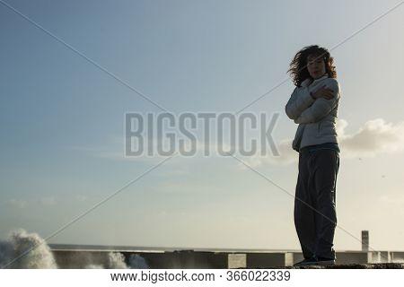 Asian woman walks along the railing of ocean promenade with a foaming surf.