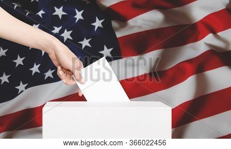 Female Voter Putting Ballot Into Voting Box On Background Us Flag. Concept Of Freedom Democracy With