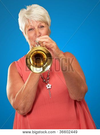 Mature Woman Blowing Her Trumpet Isolated On Blue Background