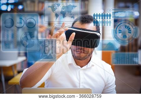 Male Student Using Vr Simulator For Training. Latin Man In Virtual Reality Glasses, Sitting At Desk