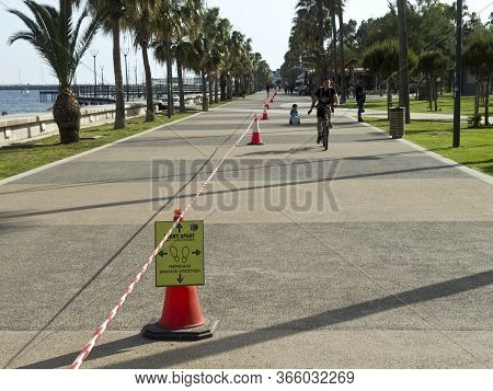 Limassol, Cyprus, May 11th, 2020: Seafront Promenade Molos With A Social Distancing Sign Board, Red