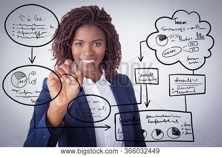 Happy Business Trainer Writing Virtual Flowchart On Glass Board With Marker. Young African American