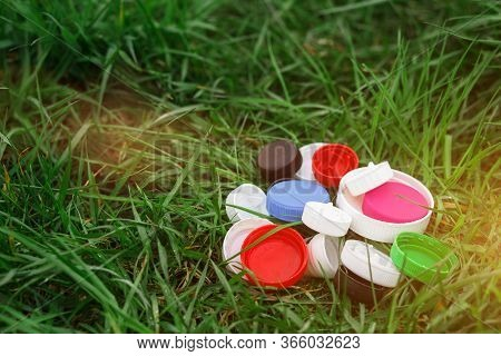 Colorful Plastic Bottle Caps On The Green Grass. Volunteer Charity Event \