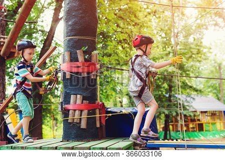 Children In Forest Adventure Park. Kids In Safety Helmets, Extreme Sport. Summer Camp. Boys Enjoy Cl