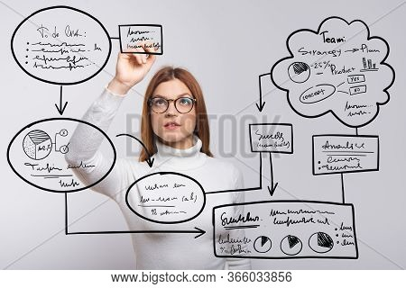 Focused Woman Writing Virtual Flowchart In Air. Concentrated Young Woman In Eyeglasses Holding Pen A